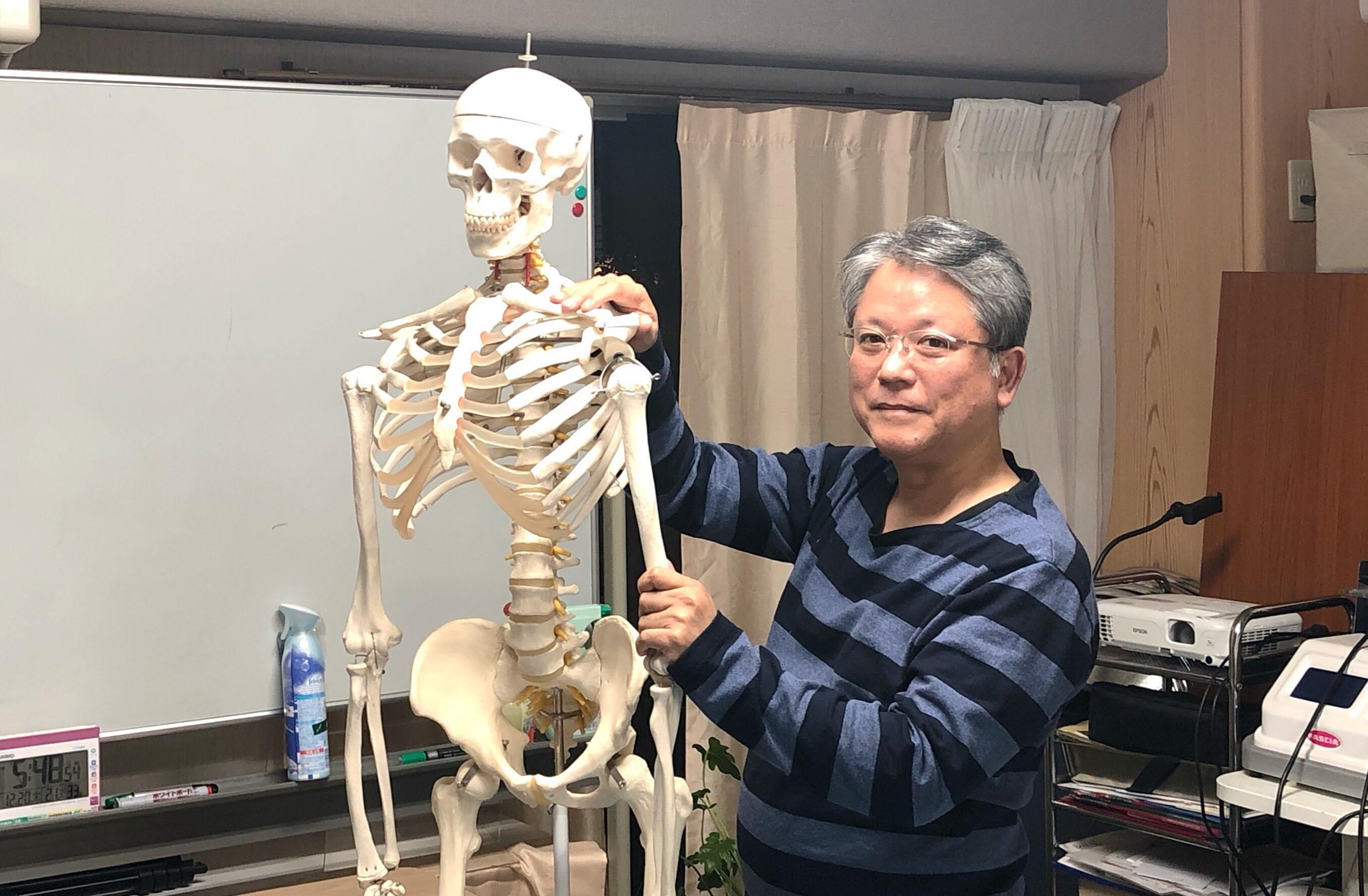 骨格模型の肩と腕に笑顔で触れる塾長